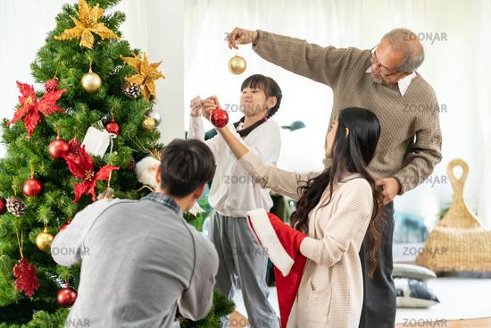 Multigenerational asian Family decorating a Christmas tree for season greeting.