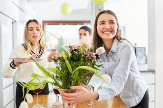 Frau mit Freundinnen beim Tisch decken für gemeinsames Mittagessen