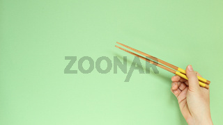 Hand holding wooden chopsticks isolated on green background. copy space
