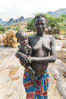 BOYA TRIBE, SOUTH SUDAN - MARCH 10, 2020: Woman in traditional colorful clothes and accessories looking at camera with interest while standing and carrying tranquil little child on hands in countryside in South Sudan