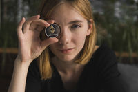 A nice girl is attaching a gold and silver ethereum coin to her eye. Bitcoins, crypto currency, electronic money. Woman sitting in cafe holding bitcoin in front eye. Virtual future currency concept. Bitcoin lover.