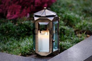 Grablaterne aus Metall mit brennender Kerze auf einem Grab