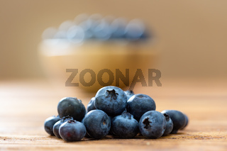 Heap of fresh blueberries lying on wooden table.