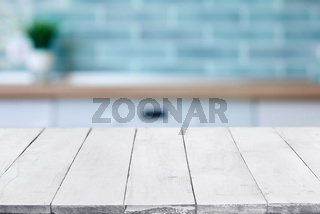 Empty white wooden boards or table top over blurred kitchen interior on background. Template, mockup for display or montage. Close up, copy space