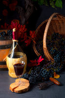 Grapes in the basket with wine and tree leaves
