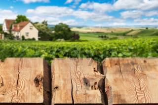 Wooden boards or countertop against blurred countryside landscape on background. Use as mockup for display or montage of your products. Close up
