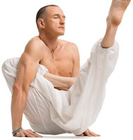 Mature shirtless muscular man practising yoga
