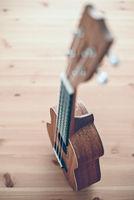 A brown soprano ukulele on wooden background