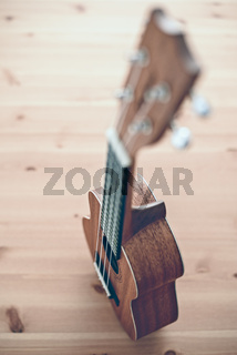 A brown soprano ukulele on wooden background