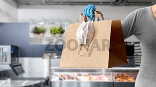 woman with food in paper bag, face mask and gloves