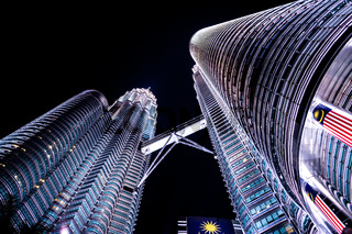 View from the ground on the beatiful light show at high building at night. World famous iconic landmark skyscrapers and the symbol of Malaysia. Illuminated building. Ahitecture. Concrete jungle.