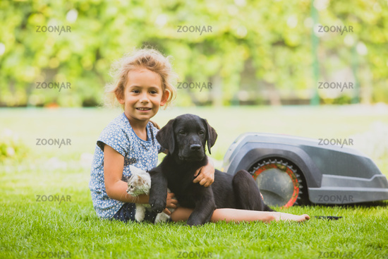 Cute liitle girl with her pets on freshly mowed lawn