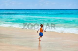 Three year old toddler boy running on beach