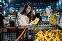 The girl with surgical mask is going to buy bananas.