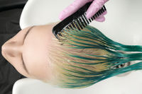 Top view of hairdresser holding wet hair in hand and combing customer long green and discolored hair while shampooing in shower