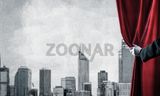Modern drawn cityscape behind drapery curtain and hand opening it