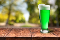 Green beer in glass on wooden table against blurred park.