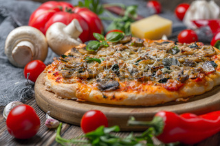 Homemade pizza with tomatoes, spinach and mushrooms.