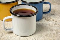 metal cup of hot tea on a ceramic tile