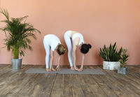 Smiling mother and daughter practicing yoga together