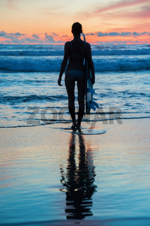 Young woman surfer with board