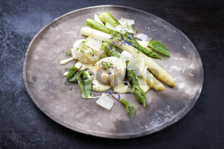 Traditional barbecue scallops with green and white asparagus and sauce hollandaise offered as close-up on a rustic modern design plate