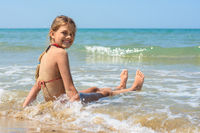 Happy girl sitting on a sandy beach and looking back smiling looked into the frame