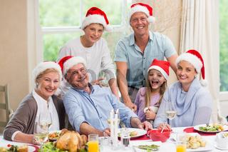 Happy family in santa hat looking at camera