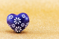 A blue heart with flower pattern isolated on a golden background