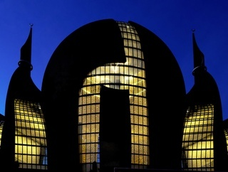 die beleuchtete Kölner Zentralmoschee in der Abenddämmerung
