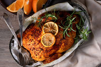 Baked whole chicken in spices with crispy appetizing fried crust in a tray, dark moody