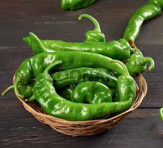 green hot pepper pods in a round wicker basket on a brown wooden table