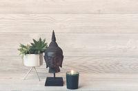 Plant and candle near Buddha head