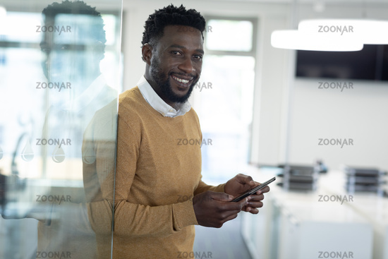 Portrait of Businessman using smartphone at modern office