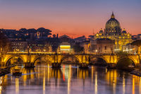 The Tiber river and St. Peters Basilica in the Vatican City, Italy, at sunset