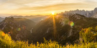 Amazing sunrise in the mountains. Backlight Sunlight with beautiful lens flares and sunbeams. Panorama Julian Alps, Triglav National Park, Slovenia, Mountain Slemenova, Sleme.