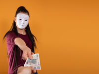 An anonymous woman stands and pulls her hand in with paper banknotes with the face value of one hundred Polish zlotys. No face because there's a mask on it.