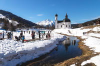 Cross-country skiers on sunny track along a river and a pitoresque church reflecting in the water