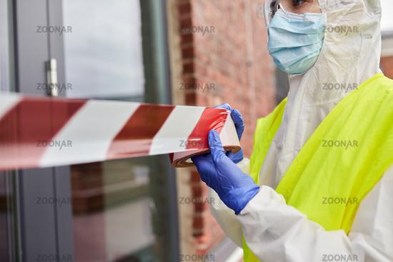 healthcare worker sealing door with caution tape