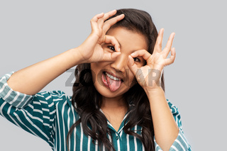 smiling asian woman looking through finger glasses