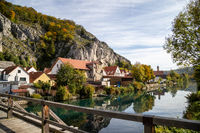 Idyllic view at the village Essing in Bavaria, Germany with the Altmuehl river, high rocks in background and a wooden bridge in the foreground