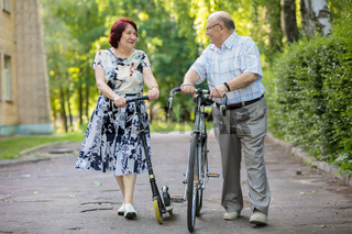 Happy elderly couple with a bicycle. Handsome man and woman senior citizens. Husband and wife of old age in the park.