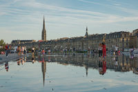 People have fun and refresh on a hot summer day, in the mirror fountain in Bordeaux, France