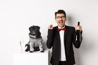 Pets, winter holidays and New Year concept. Happy young man celebrating Christmas with cute black dog wearing party costume, holding bottle champagne, white background