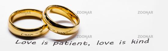 Golden wedding rings on bible phrase