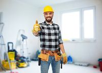 happy male worker or builder showing thumbs up