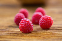 Fresh raspberries lying on wooden table from close up