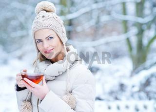 Frau trinkt Tasse Tee im Winter im Schnee