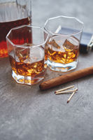 Two glasses of old whiskey with cuban cigar and carafe