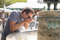 Thirsty young casual cucasian man drinking water from public city fountain on a hot summer day